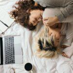 To kvinder sover sammen med bærbar