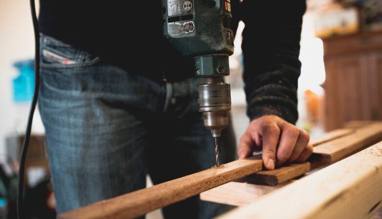 Mand borer i træ på arbejde