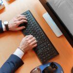 Mand skriver på computer