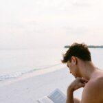 Mand sidder på strand og læser bog